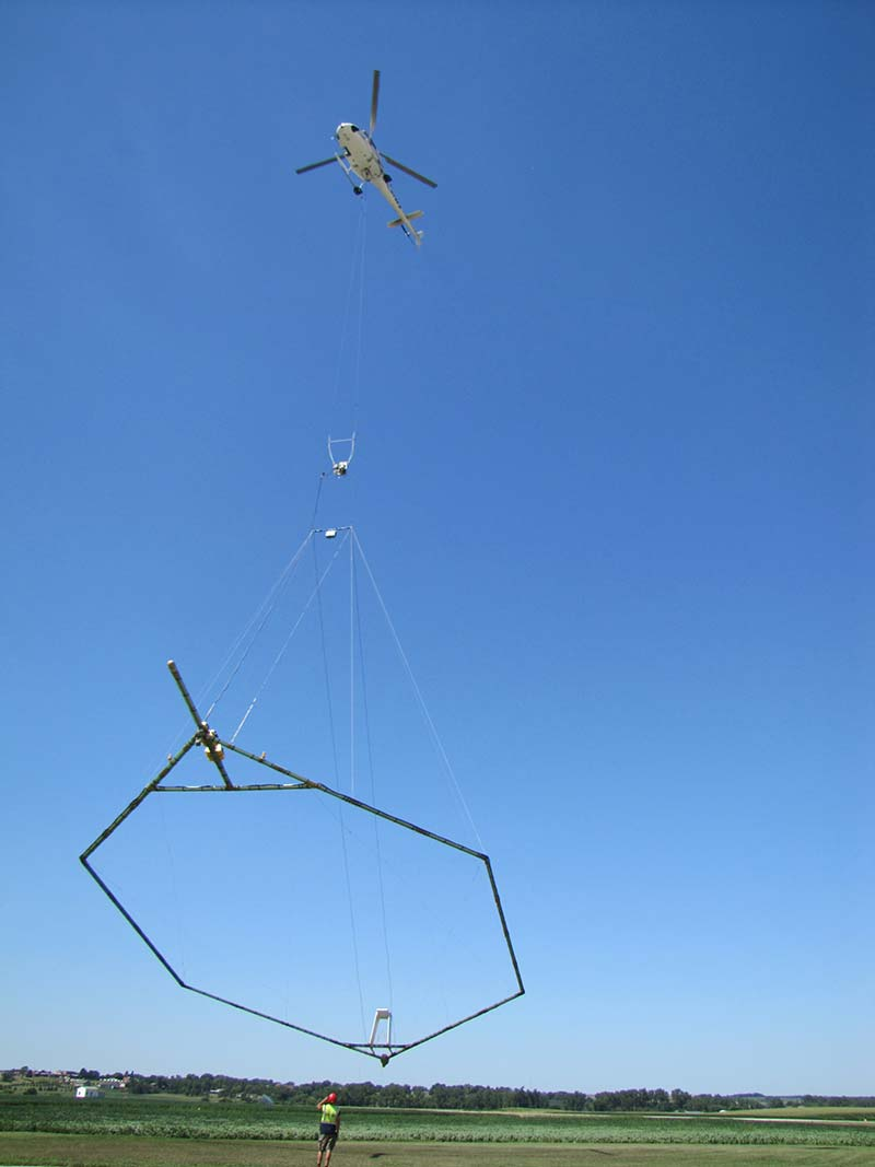 A hoop shaped geophysical device which contains sensors is suspended beneath a helicopter used to conduct surveys.