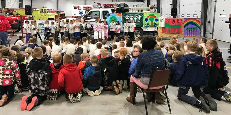 Group of children and adults learning about Arbor Day at the Fire Station.