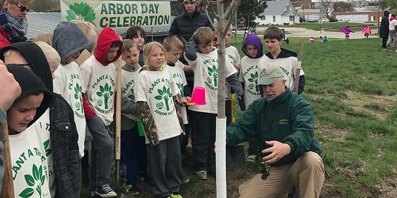 Man explaining trees to children for Arbor Day.